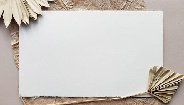 Modelli in bianco bianchi delle carte dell'invito di nozze con foglia di palma secca sul backgound strutturato della tavola. modello moderno ed elegante per l'identità del marchio. design tropicale. vista piana, vista dall'alto