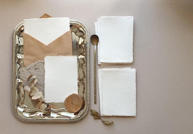 Modelli in bianco bianchi delle carte dell'invito di saluto di nozze con la busta del mestiere, foglie secche dell'eucalyptus sul backgound strutturato della tavola. modello moderno ed elegante per l'identità del marchio. vista piana, vista dall'alto