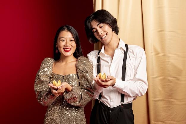 Modelli sorridenti che tengono i biscotti di fortuna per il nuovo anno cinese