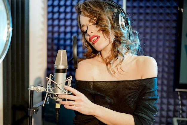 Modello abbastanza fantastico con le cuffie davanti al microfono in studio di registrazione. la giovane signora sexy che posa in cuffie si avvicina al mic in vestito nero.