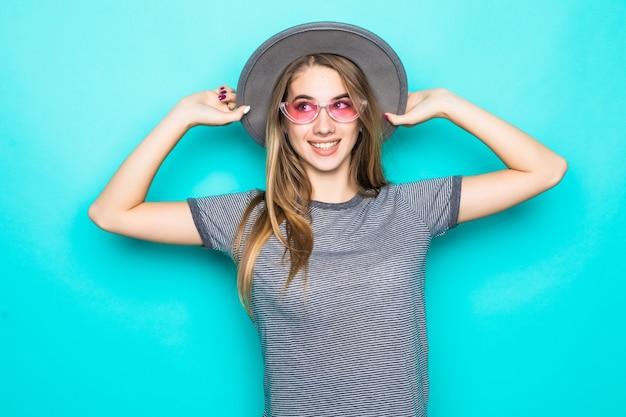 Modello abbastanza giovane in t-shirt moda, cappello e occhiali trasparenti isolati su sfondo verde