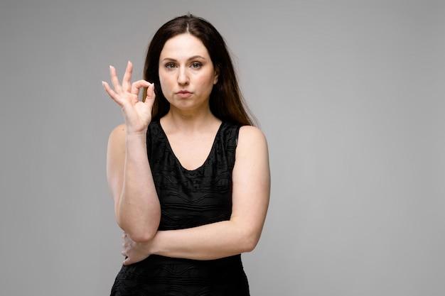 Modello abbastanza grande emozionale abbastanza serio che sta nello studio che mostra gesto giusto su fondo grigio
