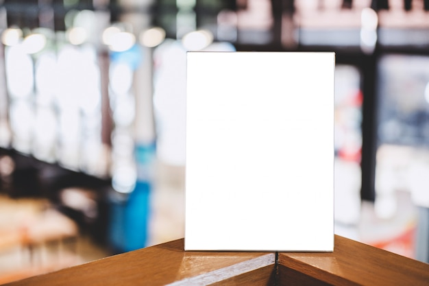 Modello acrilico della struttura in bianco, struttura del menu in bianco sulla tavola in caffetteria o ristorante