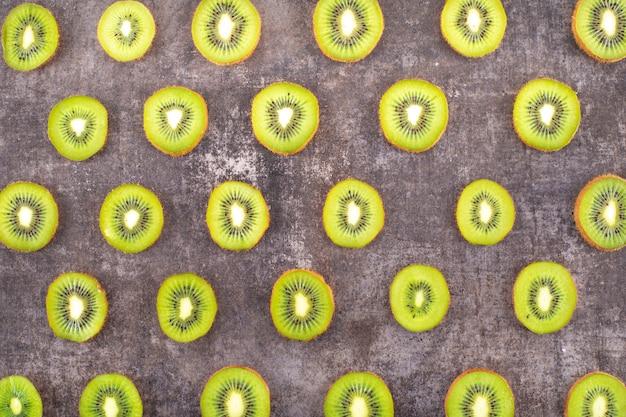 Modello affettato di vista superiore del kiwi sulla superficie grigia della pietra