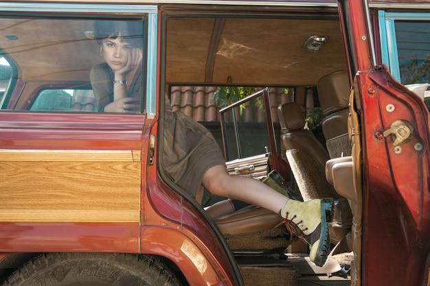 Modello alla moda che posa con confidenza in un'automobile un giorno soleggiato luminoso