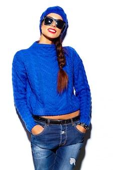 Modello alla moda di bella giovane donna alla moda con le labbra rosse in panno blu hipster maglione in berretto