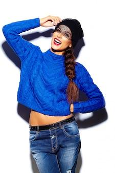 Modello alla moda di bella giovane donna alla moda con le labbra rosse in panno blu hipster maglione