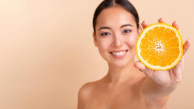 Modello asiatico del primo piano con l'arancia e lo copia-spazio