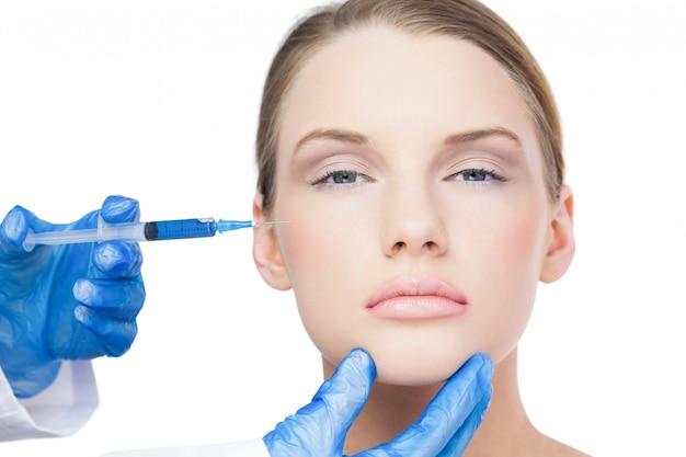 Modello attraente contenuto con iniezione di botox sulla guancia