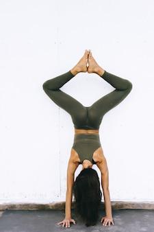 Modello attraente facendo esercizi di yoga su sfondo bianco in vestiti sessuali