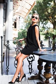 Modello attraente in abito corto nero che si appoggia sul tavolo sulla terrazza. sta cercando di fotocamera.