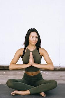 Modello attraente in posa yoga su sfondo bianco in vestiti sessuali