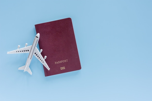 Modello bianco dell'aeroplano con il passaporto sull'azzurro per il concetto di viaggio e di viaggio