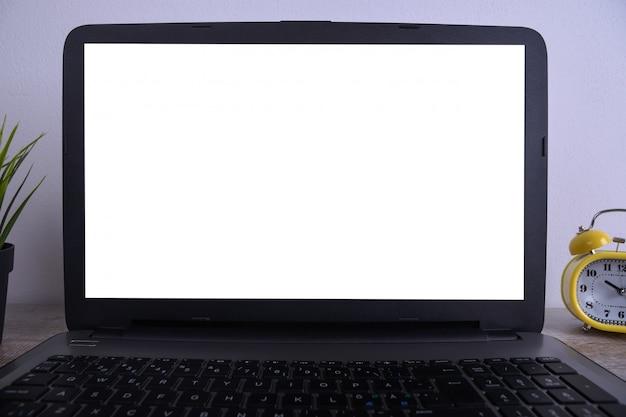 Modello bianco moderno della tavola della scrivania, spazio di lavoro con il computer portatile con lo schermo bianco per voi testo o immagine, erba verde, tazza di caffè e una pila di carte sul fondo bianco della roccia.
