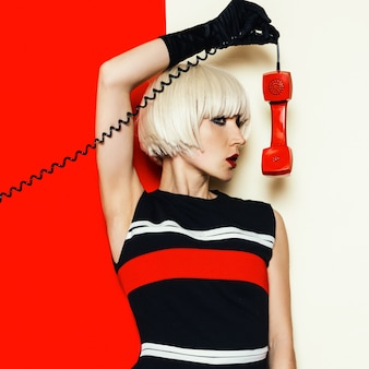 Modello biondo stile retrò con telefono vintage moda minimale