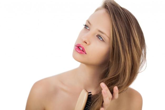 Modello brunetta da sogno che si spazzola i capelli