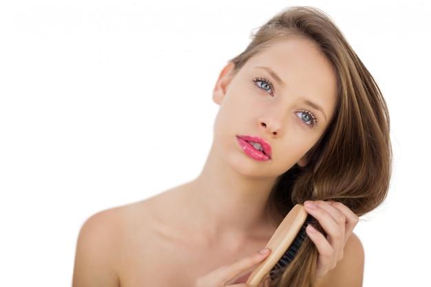 Modello brunetta premuroso che spazzola i suoi capelli