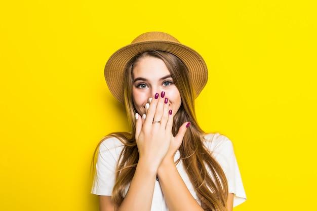 Modello carino in maglietta bianca e cappello tra sfondo arancione coprire la bocca con la mano