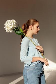 Modello carino in posa con il fiore