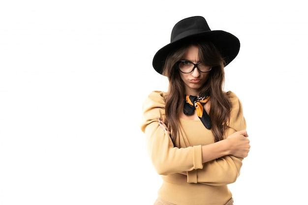 Modello castana offensivo con occhiali, cappello e fazzoletto da collo in posa sul muro bianco