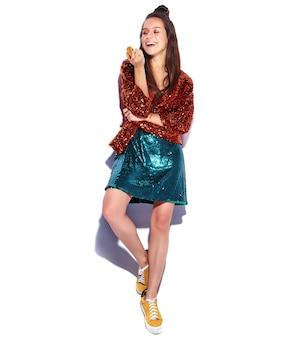 Modello castana sorridente caucasico bello della donna dei pantaloni a vita bassa in rivestimento alla moda di estate di riflessione shinny luminosa e vestito verde isolati. mangiare amaretto francese