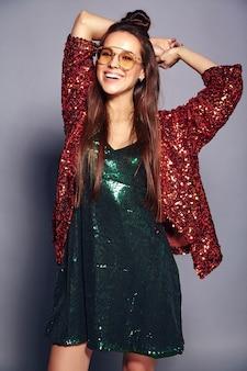 Modello castana sorridente caucasico bello della donna dei pantaloni a vita bassa in rivestimento elegante di estate shinny di riflessione brillante e vestito verde che posano sul gray