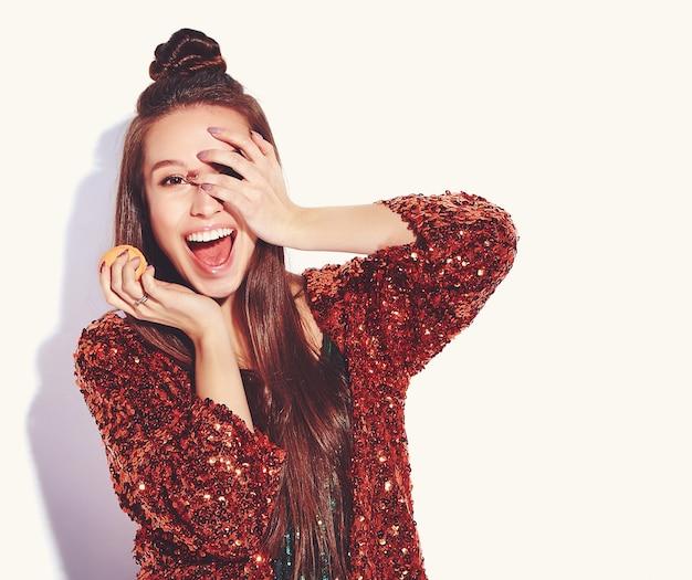Modello castana sorridente sorpreso bei caucasici dei pantaloni a vita bassa in rivestimento alla moda di estate shinny di riflessione brillante brillante e vestito verde isolati. mangiare amaretto francese