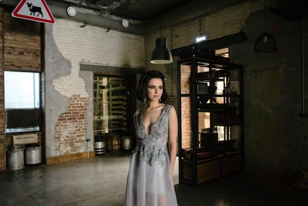 Modello che propone in un abito da sposa lungo bianco al chiuso dalla finestra.