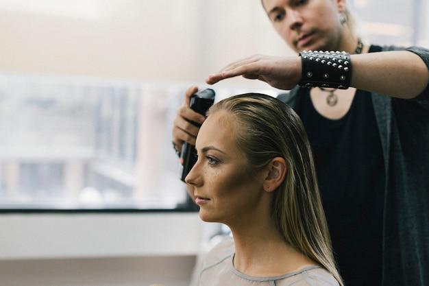 Modello che si fa fare i capelli da uno stilista