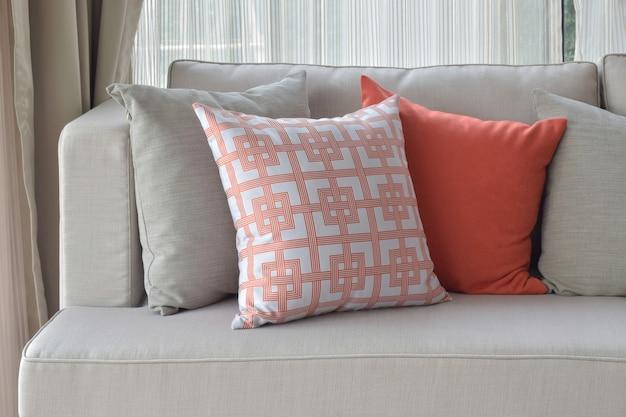 Modello cinese in arancione con cuscini arancioni e grigi su divano grigio chiaro