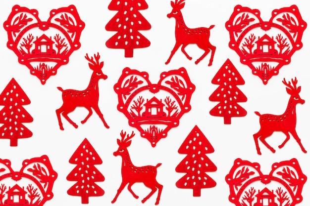Modello con cuore di legno rosso con silhouette di casa, cervi e abete. decorazioni natalizie rosse ornamentali.