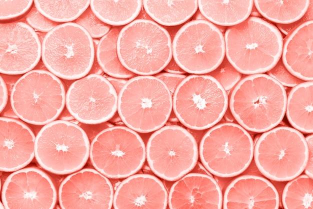 Modello creativo. struttura fresca della frutta arancio affettata. macro, vista dall'alto con spazio di copia. cornice alimentare. arance succose nel fondo di colore di corallo.