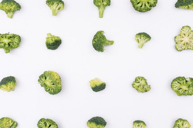 Modello dei broccoli sistemato fila per fila su superficie bianca