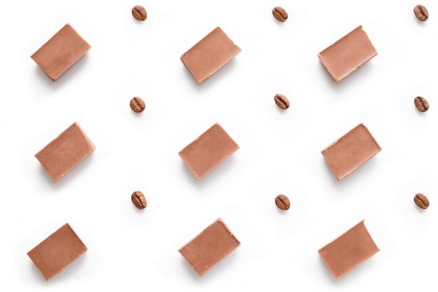 Modello dei mattoni del cioccolato con i chicchi di caffè sulla vista superiore bianca