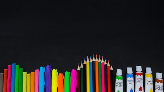 Modello dei rifornimenti di scuola sul fondo della lavagna con copyspace