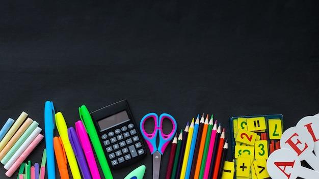 Modello dei rifornimenti di scuola sul fondo della lavagna