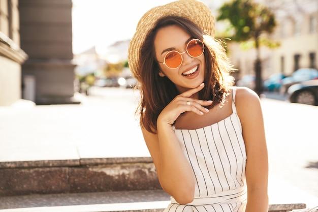 Modello del brunette in vestiti di estate che propongono sulla posa della via