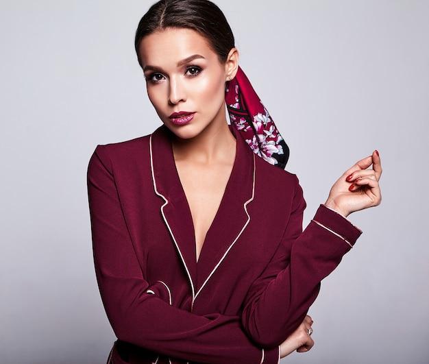 Modello del brunette in vestito rosso con trucco di sera su gray