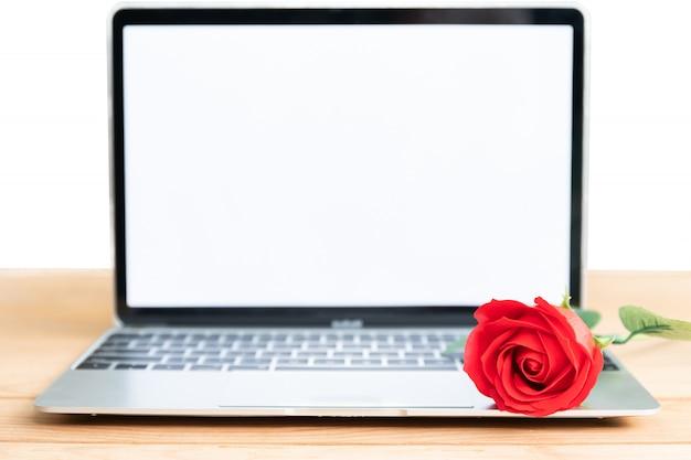 Modello del computer portatile e della rosa rossa su bianco