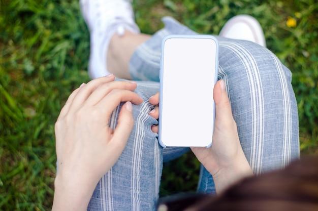 Modello del telefono cellulare della tenuta della mano femminile con lo schermo in bianco
