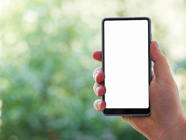 Modello del telefono della tenuta della mano con fondo defocused