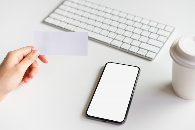 Modello della carta e dello smartphone della tenuta della donna che tiene lo schermo in bianco sulla tavola.