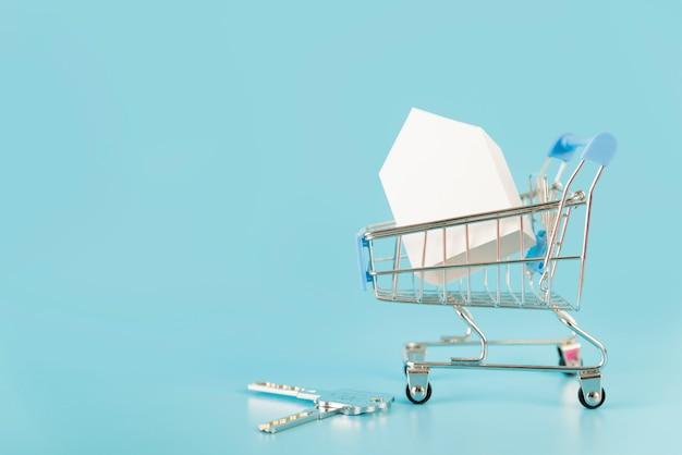 Modello della casa del libro bianco dentro il carrello con le chiavi contro fondo blu