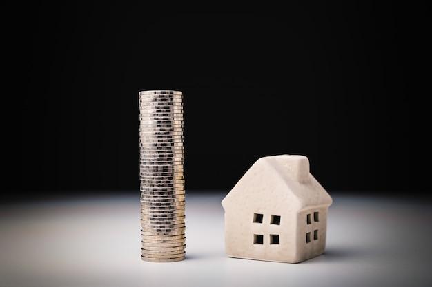 Modello della casa e fila di soldi della moneta sulla tavola bianca