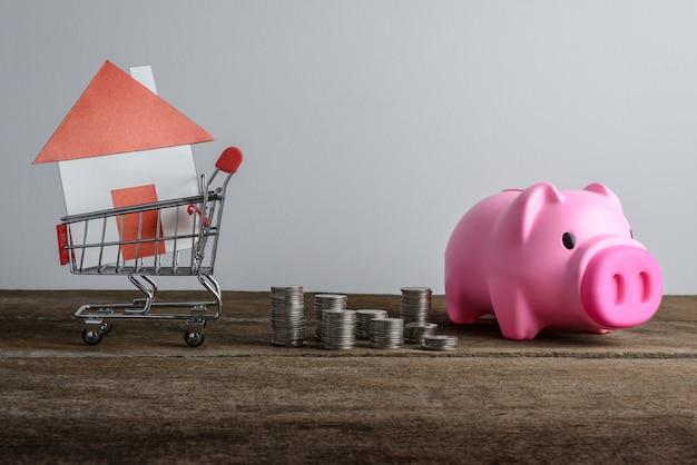 Modello della casa nel carrello e fila di soldi della moneta e porcellino salvadanaio