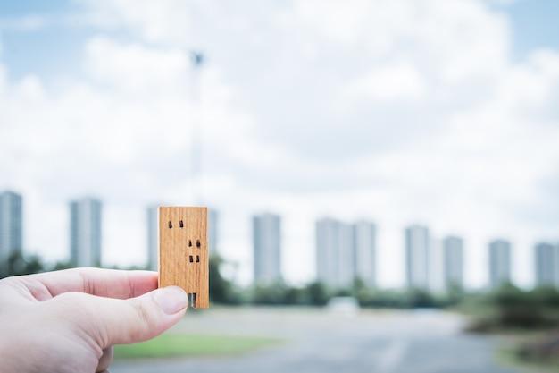 Modello della casa nella mano dell'agente di brokeraggio assicurativo domestico o nella persona del venditore.