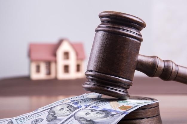 Modello della casa sui dollari dei soldi con il martello di un giudice come ipoteca di concetto di investimento