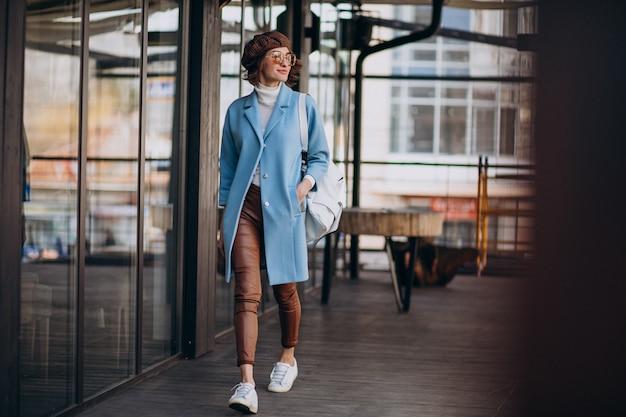 Modello della giovane donna in cappotto blu dal caffè