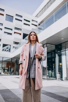 Modello della giovane donna in cappotto rosa dall'edificio