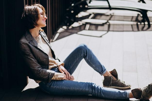 Modello della giovane donna in rivestimento che posa fuori
